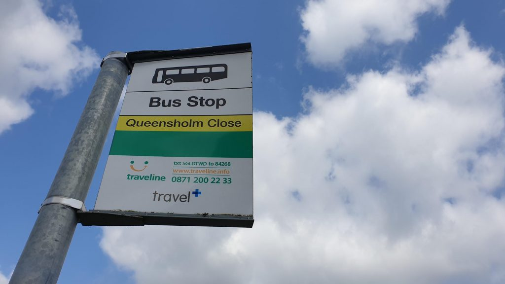 Bus stop sign against background of sky.